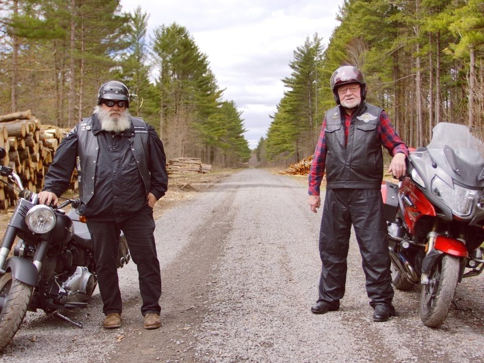 two men standing beside eachother with their motorcycle